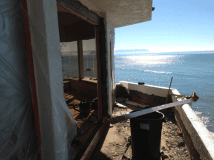 A deck in the midst of being repaired--it overlooks the ocean